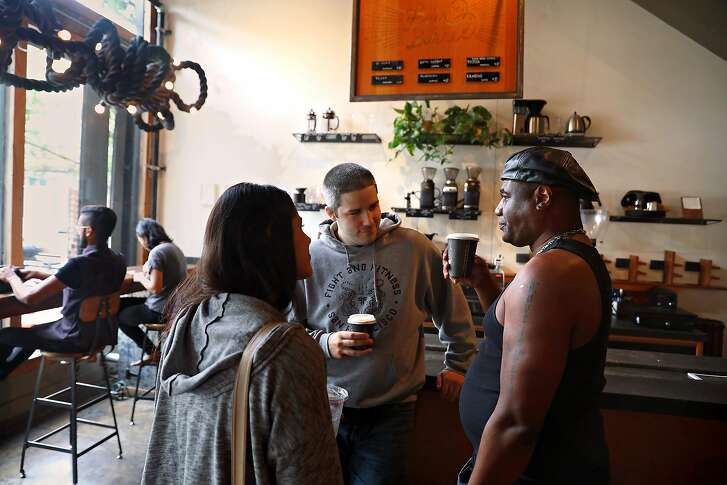 Jennifer Mays (left) from San Francisco and Joe Chernay (middle) from San Francisco have coffee with Milton Davis (right) from New Jersey at Four Barrel coffee on Wednesday, Aug. 15, 2018 in San Francisco, Calif.
