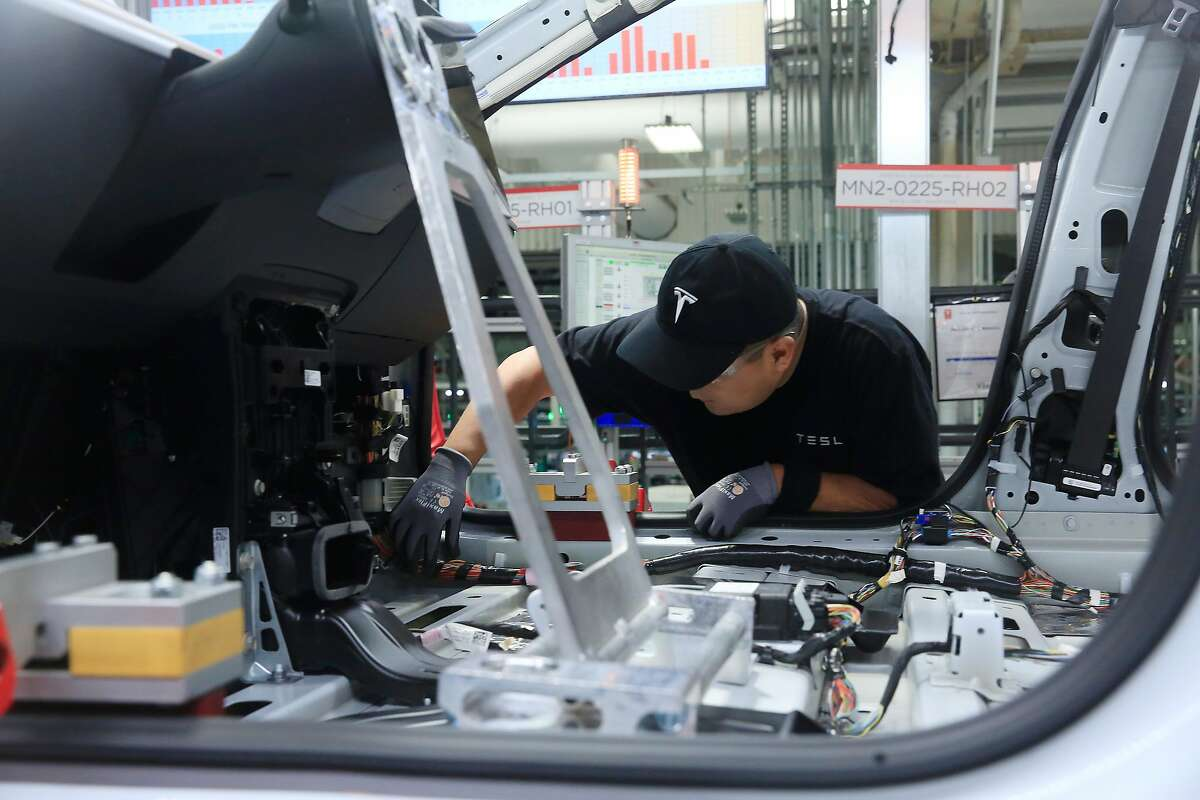 A production associate works on a Tesla Model 3 at the Tesla factory on Wednesday, July 18, 2018 in Fremont, Calif.