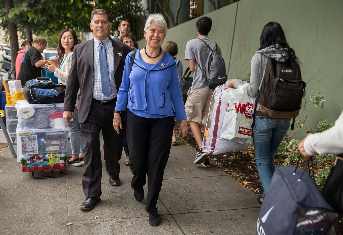 UC Berkeley Chancellor Carol Christ walks by new students and parents as they haul belongings into the Unit 1 Residential Hall during move-in day at the dorms in Berkeley, Calif. Tuesday, Aug. 14, 2018.