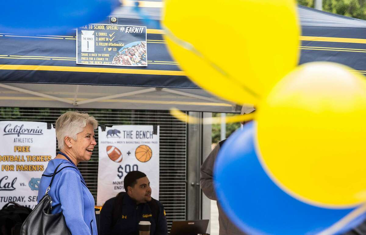 UC Berkeley Chancellor Carol Christ checks out the athletics program while greeting new students and parents during move-in day at the Unit 2 Residential Hall in Berkeley, Calif. Tuesday, Aug. 14, 2018.