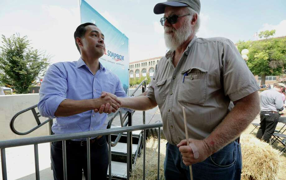 Former Housing and Urban Development Secretary Julian Castro talks with Mark Winslow, of Corydon, Iowa, right, during a visit to the Iowa State Fair, Friday, Aug. 17, 2018, in Des Moines, Iowa. Castro, considering a 2020 presidential bid, was at the state fair to speak at The Des Moines Register Political Soapbox. (AP Photo/Charlie Neibergall) Photo: Charlie Neibergall, Associated Press / Copyright 2018 The Associated Press. All rights reserved