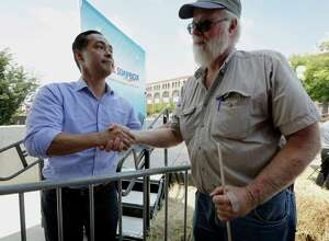 Former Housing and Urban Development Secretary Julian Castro talks with Mark Winslow, of Corydon, Iowa, right, during a visit to the Iowa State Fair, Friday, Aug. 17, 2018, in Des Moines, Iowa. Castro, considering a 2020 presidential bid, was at the state fair to speak at The Des Moines Register Political Soapbox. (AP Photo/Charlie Neibergall)