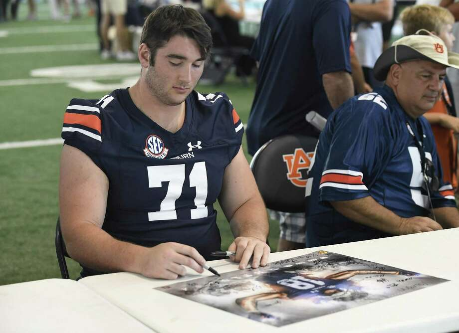 Madison's Jack Driscoll signs a poster during Auburn Fan Day on Aug. 11 in Auburn, Ala. Photo: Todd Van Emst / Auburn Athletics / Todd Van Emst/AU Athletics