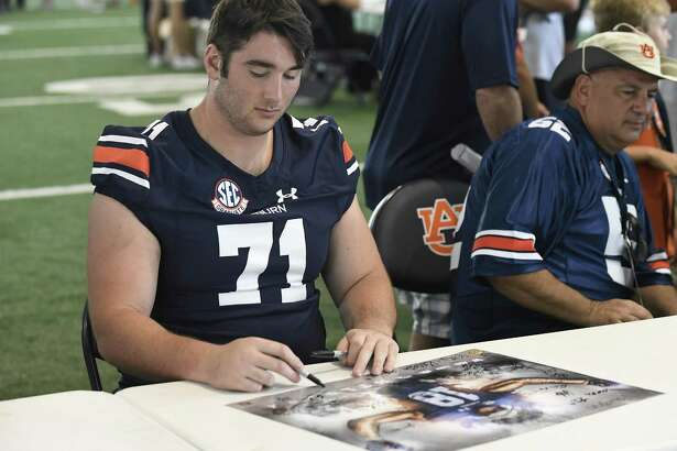 Madison's Jack Driscoll signs a poster during Auburn Fan Day on Aug. 11 in Auburn, Ala.