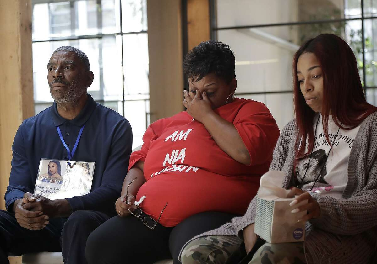 Ansar El Muhammad, the father of Nia Wilson, left, listens during a news conference with Wilson's mother Alicia Grayson, center, and Wilson's sister Tashiya Wilson in San Francisco, Friday, Aug. 17, 2018. The family of Nia Wilson who was fatally stabbed at an Oakland train station is taking first legal step toward suing the Northern California public transit system. Attorney Robert Arns said his law firm delivered a legal claim Friday to the Bay Area Rapid Transit on behalf of the family of 18-year-old Wilson. (AP Photo/Jeff Chiu)