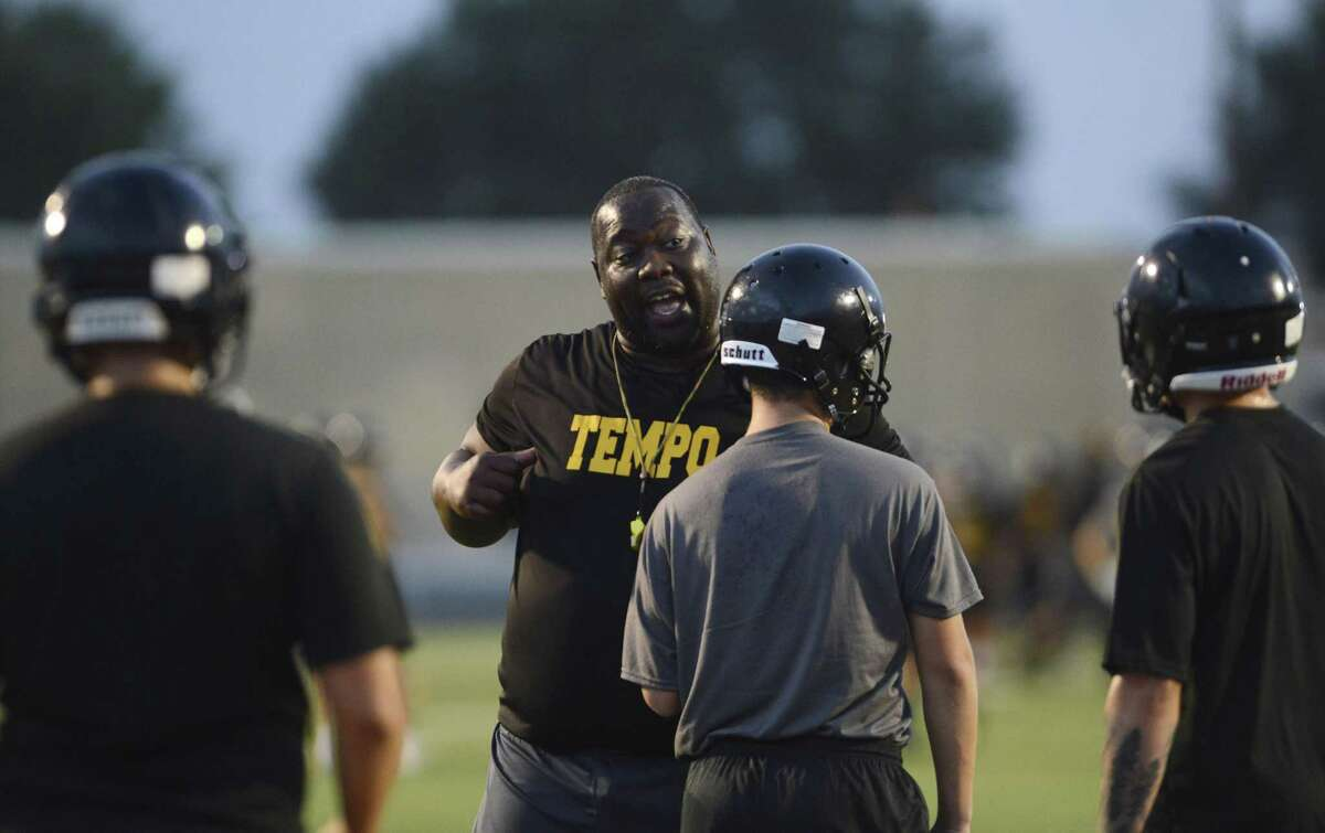 Football coach Joe Hubbard of the East Central Hornets advises his team during a blocking drill at an early morning practice on Tuesday, Aug. 14, 2018. Hubbard is an early adopter of a program called