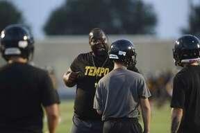 Football coach Joe Hubbard of the East Central Hornets advises his team during a blocking drill at an early morning practice last week. The school district's board Thursday adopted a $126 million budget based on a property tax rate slightly lower than the current year's.