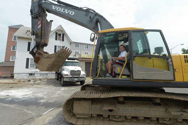 Property owner Jason Milligan awaits Northeast Excavating to start the demolition of the home at 21 Isaacs Street Friday August 17, 2018, in the Wall Street redevelopment area in Norwalk, Conn. Milligan had received a demolition permit for the work even though the city?'s lawyer subsequently tried to get the permit voided in their ongoing legal dispute.