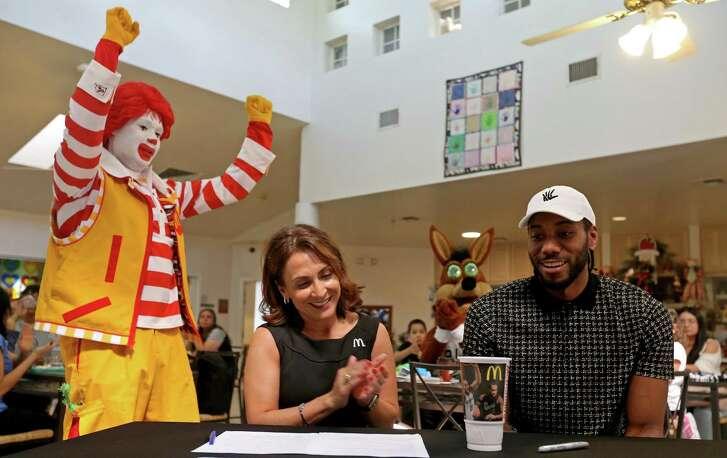 Local McDonald's owner/operator Celia Jairala (center left) and San Antonio Spurs' Kawhi Leonard unveil the 2017 Spurs Kawhi Leonard Keepsake Cup during a press conference held March 24, 2017 at the Ronald McDonald House Charities of San Antonio.