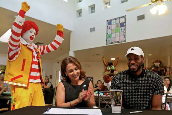 Local McDonald's owner/operator Celia Jairala (center left) and San Antonio Spurs' Kawhi Leonard unveil the 2017 Spurs Kawhi Leonard Keepsake Cup during a press conference held March 24, 2017 at the Ronald McDonald House Charities of San Antonio.