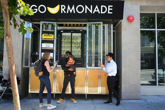 Vicktor Stevenson (center), owner of Gourmonade, talks with customer Christine Friel (left) of Oakland while he holds his son Legacy Stevenson, 10 months, as he works with partner Axel Estanislao (right)  at the Gourmonade stand on Valencia Street  on Friday, August 18,  2018 in San Francisco, Calif.