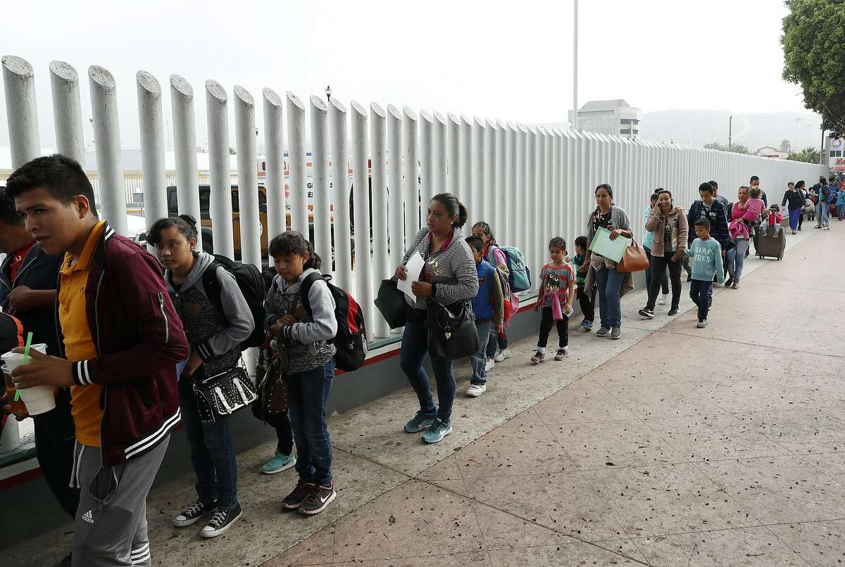 """FILE - In this Thursday, July 26, 2018 photo people line up to cross into the United States to begin the process of applying for asylum near the San Ysidro port of entry in Tijuana, Mexico. A federal judge has extended a freeze on deporting families separated at the U.S.-Mexico border, giving a reprieve to hundreds of children and their parents to remain in the United States. U.S. District Judge Dana Sabraw said in his order Thursday, Aug. 16, 2018, that """"hasty"""" deportation of children after reunification with their parents would deprive them of their right to seek asylum. (AP Photo/Gregory Bull,File)"""