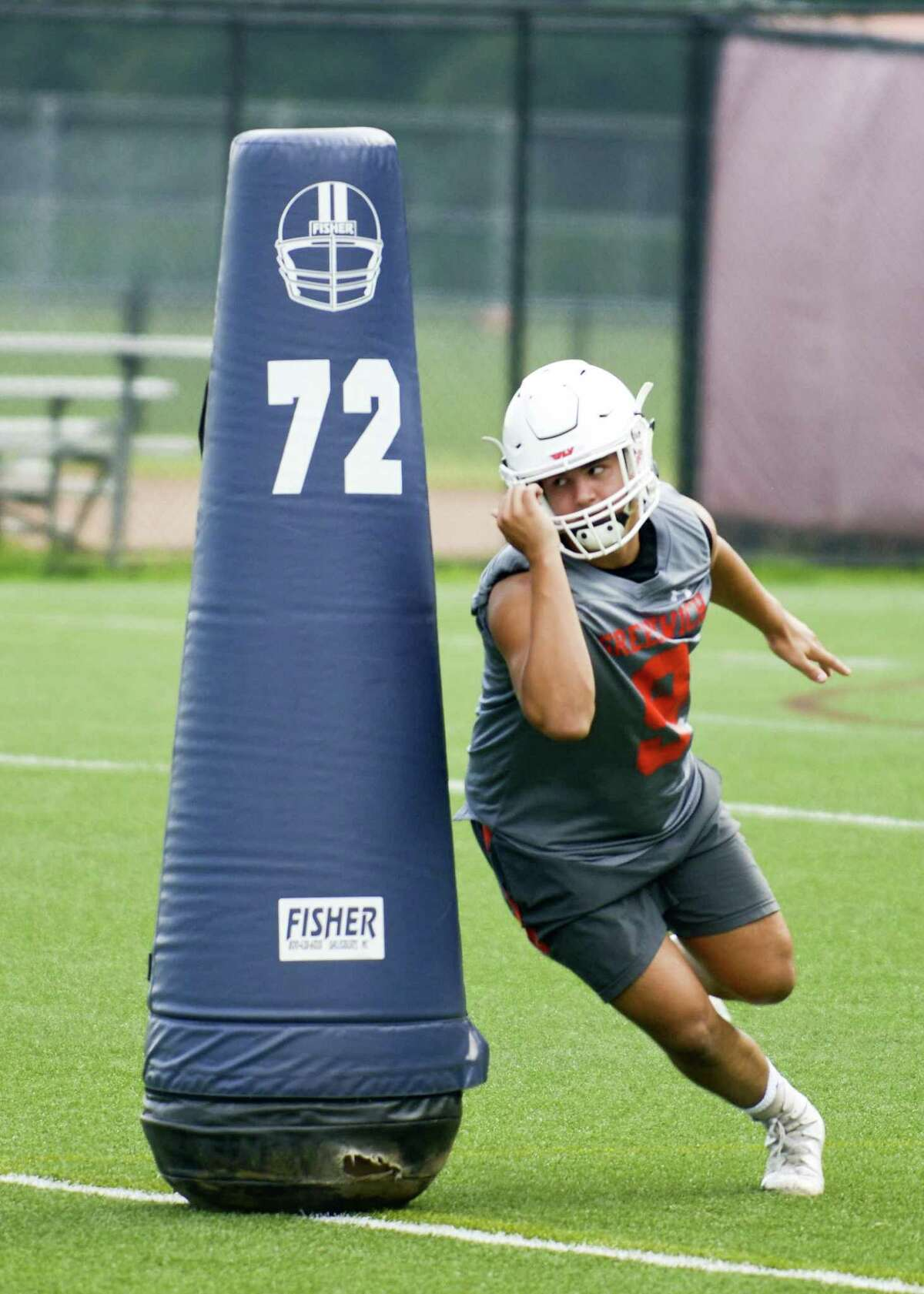 Defensive end Emilio Camou runs around a blocking dummy during a conditioning drill.