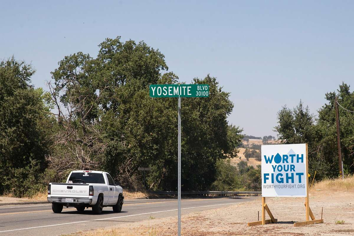 A truck drives past one of many signs challenging the state water board's controversial decision to release more water from La Grange Dam into the Tuolumne River in La Grange, Calif. Friday, Aug. 17, 2018.