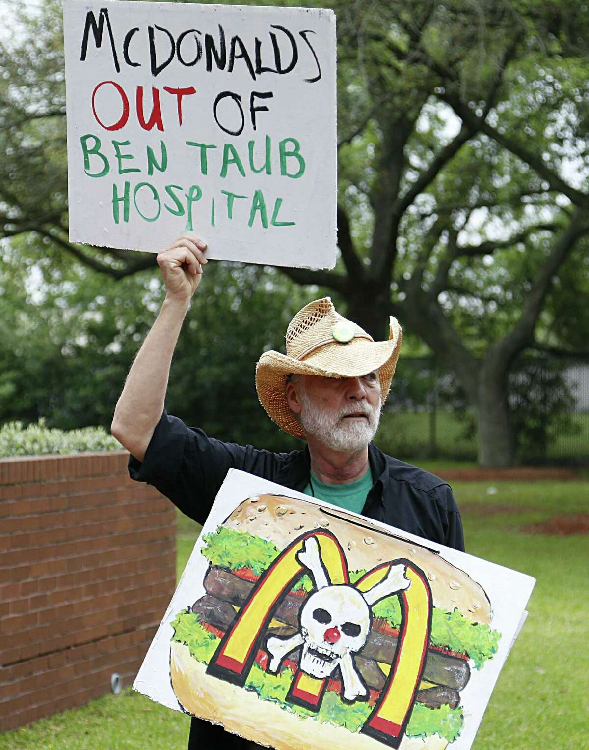 Value the Meal volunteer Don Cook holds up signs while demonstrating in front of Harris Health after presenting a petition to the board to remove McDonald's from Ben Taub Hospital Thursday, March 31, 2016, in Houston. ( James Nielsen / Houston Chronicle )