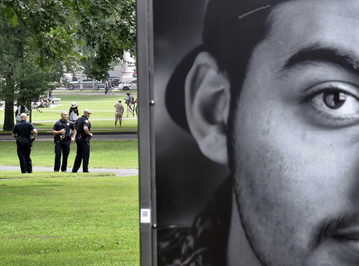 New Haven Police Officers Brendan Hawley, Michael Danielle and John Caron keep a sharp eye on the New Haven Green Friday morning in response to the epidemic of drug overdoses last week from K2, a synthetic marijuana. At right is a small billboard-size photo from an exhibit about immigration.