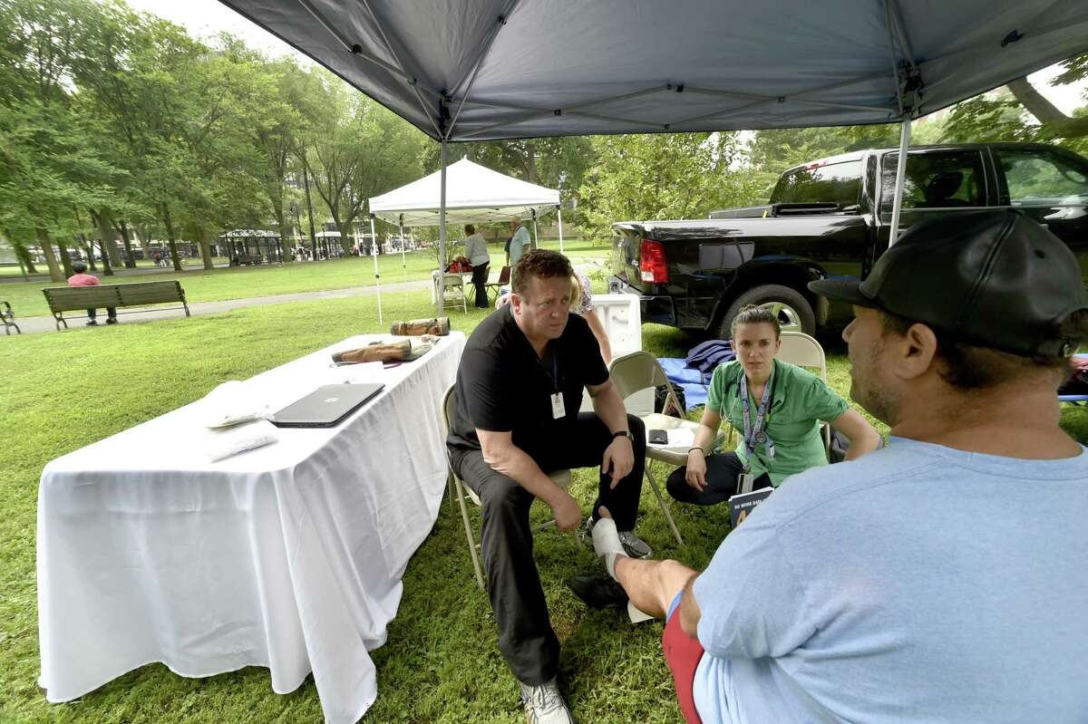 Nurse practitioner Philip Costello, clinical director of homeless care at the Cornell Scott Hill Health Center, left, with Dr. Emily Pinto Taylor of Yale New Haven Hospital, inspect the foot of a passerby on the New Haven Green Friday morning, the site of an an epidemic drug overdose from K2, a synthetic marijuana.