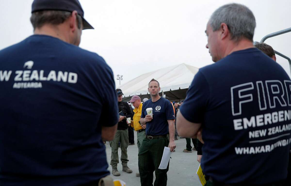 New Zealand firefighter Peter Wakeling listens to his colleagues before the command briefing at the Incident Command Post for the Mendocino Complex Fire in Ukiah, Calif., on Tuesday, August 14, 2018.