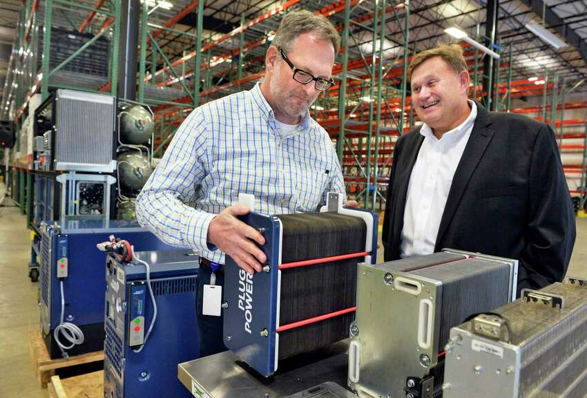 Materials manager Chris Jacobs, left, and company COO Keith Schid with their new metal stack increasing power density by 3 times over previous units during the opening of Plug Power's new warehouse and fuel cells assembly facility Friday August 17, 2018 in Clifton Park, NY. (John Carl D'Annibale/Times Union)
