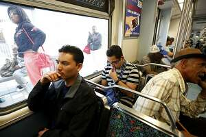 In this Feb. 15, 2017 photo, Phal Sok, left, rides the Metro Blue Line train in Los Angeles to visit with his brother in Long Beach, Calif. California Gov. Jerry Brown announced Friday, Aug. 17, 2018, he pardoned three former prisoners facing the threat of deportation to Cambodia, including Sok. Sok served 15 years for a Los Angeles County armed robbery and now works for criminal justice reform. (Genaro Molina/Los Angeles Times via AP)