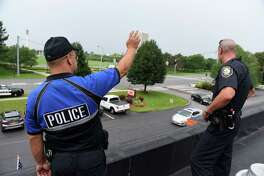 Albany police officers, Brian Hawley, left, and Derrick Schultz, right, wave to motorist from the roof of a Dunkin' Dotnuts to help raise money for Special Olympics New York on Friday, Aug. 17, 2018, on Washington Ave. in Albany, N.Y. Special Olympics athletes collected donations from several area locations to help support the cost of their athletic training and future competitions. (Will Waldron/Times Union)