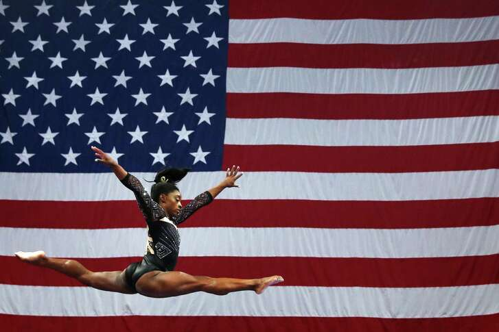 With an outsized U.S. flag as a backdrop that reflects her gymnastics skills, Spring's Simone Biles warms up on the balance beam during the second day of the USA Gymnastics national championships at TD Garden in Boston.