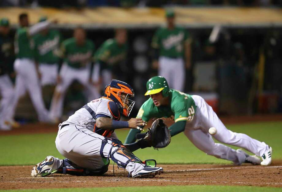 Oakland Athletics' Ramon Laureano, right, starts his slide as Houston Astros catcher Martin Maldonado waits for the ball in the ninth inning of a baseball game Friday, Aug. 17, 2018, in Oakland, Calif. Laureano scored on a double by Nick Martini. (AP Photo/Ben Margot) Photo: Ben Margot, Associated Press / Copyright 2018 The Associated Press. All rights reserved.