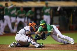 Oakland Athletics' Ramon Laureano, right, starts his slide as Houston Astros catcher Martin Maldonado waits for the ball in the ninth inning of a baseball game Friday, Aug. 17, 2018, in Oakland, Calif. Laureano scored on a double by Nick Martini. (AP Photo/Ben Margot)