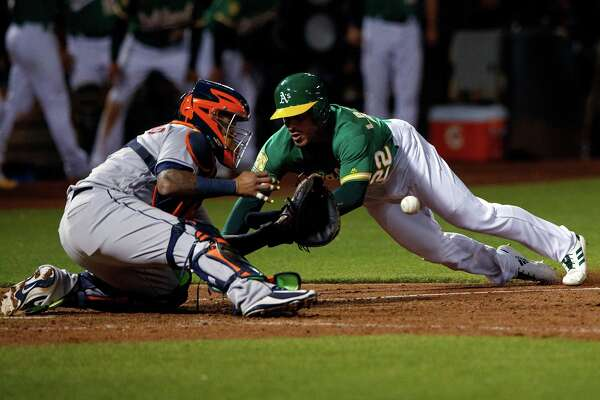 The A's Ramon Laureano, right, starts his slide into home as Astros catcher Martin Maldonado awaits the relay from Carlos Correa in the ninth inning.