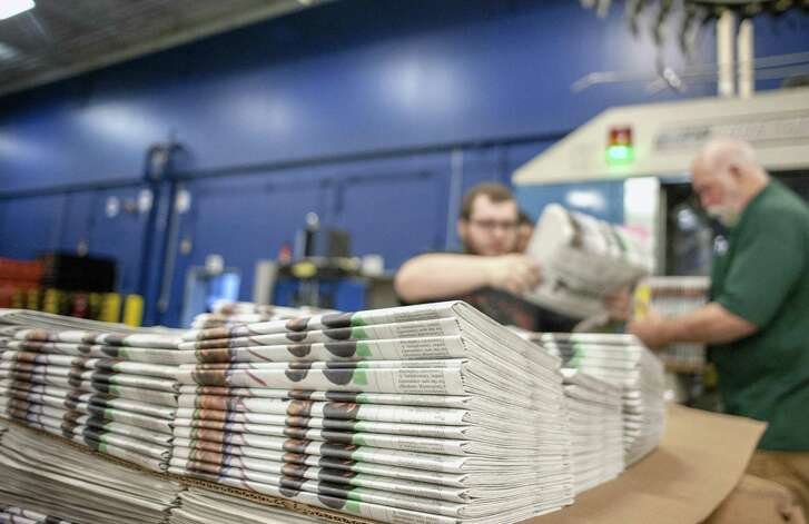 Production workers stack newspapers onto a cart in Janesville, Wis.