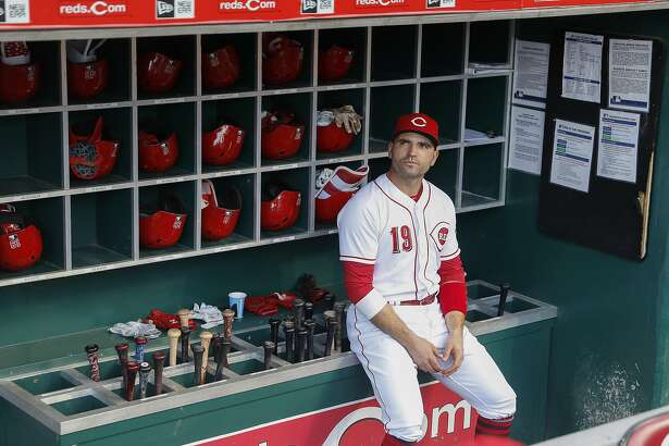 Cincinnati Reds first baseman Joey Votto sits in the dugout before a baseball game against the Philadelphia Phillies, Friday, July 27, 2018, in Cincinnati. (AP Photo/John Minchillo)