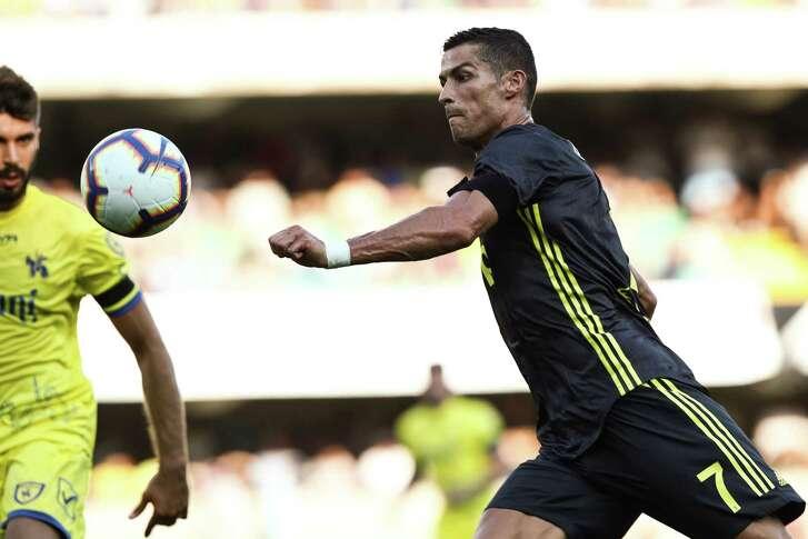 Juventus' Portuguese forward, Cristiano Ronaldo (R) eyes the ball during the Italian Serie A football match AC Chievo vs Juventus at the Marcantonio-Bentegodi stadium in Verona on August 18, 2018. (Photo by Isabella BONOTTO / AFP)ISABELLA BONOTTO/AFP/Getty Images