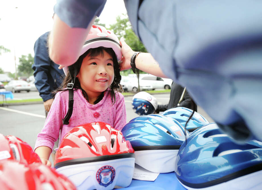 Yunhui Ma, 5, of Jericho, N.Y., gets fitted for a bike helmet during the Stamford EMS and Safety4Kids summer safety event, Bike Safety Roundup, at Chelsea Piers in Stamford, Conn., Saturday, August 18, 2018. One-hundred children received free bike helmets courtesy of Stamford EMS and Cross Insurance of Stamford as well as receiving basic bicycle safety lessons and basic bike repair. Photo: Bob Luckey Jr., Hearst Connecticut Media / Greenwich Time