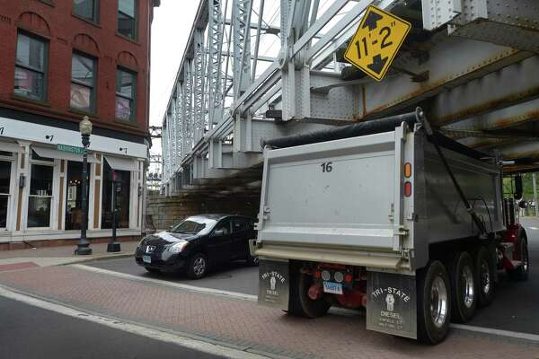Trucks drive under the Metro-North Railroad Bridge at the intersection of Washington and North and South Main streets Friday in Norwalk . Trucks that exceed the clearance strike the bridge at least once a month.