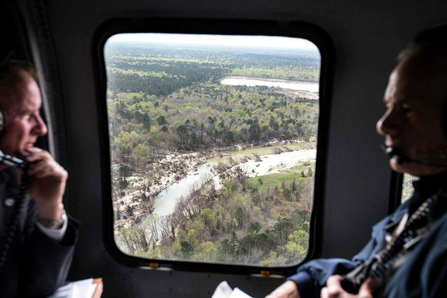 Sand can be seen piled on the banks of the San Jacinto River as Dave Martin, Houston city councilman, District E, left, and Gov. Greg Abbott take an aerial tour over the river, downstream from Lake Conroe, on Thursday, March 15, 2018, in Houston. The Kingwood area suffered serious flooding during Hurricane Harvey due in part to sand washed downstream from sand mining operations along the river. ( Brett Coomer / Houston Chronicle ) Photo: Brett Coomer, Staff / Houston Chronicle / © 2018 Houston Chronicle