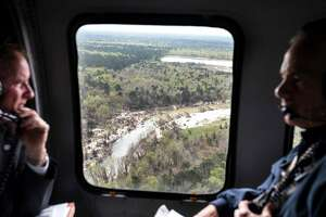 Sand can be seen piled on the banks of the San Jacinto River as Dave Martin, Houston city councilman, District E, left, and Gov. Greg Abbott take an aerial tour over the river, downstream from Lake Conroe, on Thursday, March 15, 2018, in Houston. The Kingwood area suffered serious flooding during Hurricane Harvey due in part to sand washed downstream from sand mining operations along the river. ( Brett Coomer / Houston Chronicle )