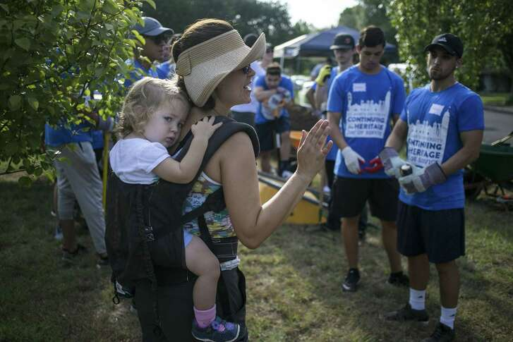 Caroline Attwood, steward of Jefferson Community Garden, carries 1-year-old daughter Michelle on her back as she gives volunteers guidance.