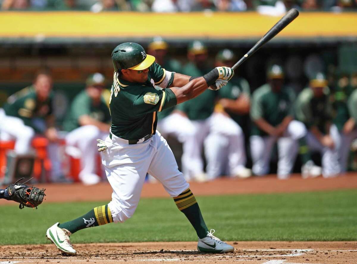 Oakland Athletics' Khris Davis follows through on his swing after hitting a two-run double off Houston Astros pitcher Dallas Keuchel in the first inning of a baseball game Saturday, Aug. 18, 2018, in Oakland, Calif. (AP Photo/Ben Margot)