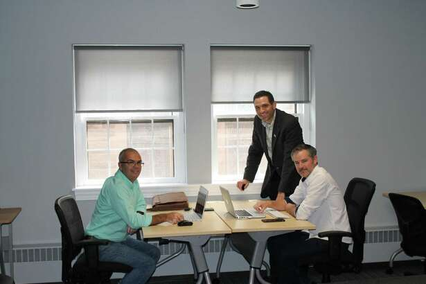 Middlesex County Chamber Vice President Jeff Pugliese, standing, talks with Tim Laubacher, left, and Ryan McAraw of Sound Web Solutions as they work in the MEWS+ in Middletown.