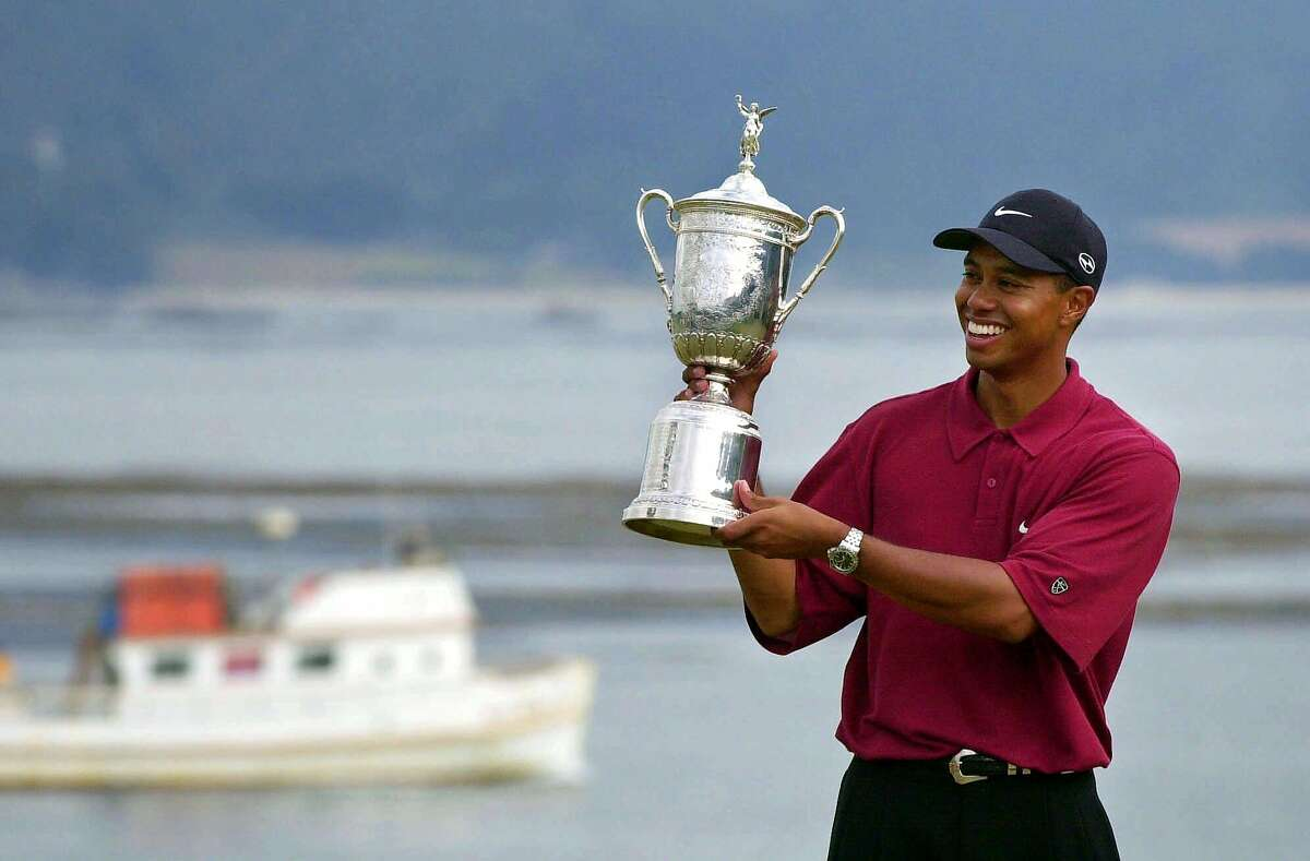 Tiger Woods shows off his winner's trophy after capturing the 100th U.S. Open Golf Championship at the Pebble Beach Golf Links in Pebble Beach, Calif., Sunday, June 18, 2000. Woods won with a score of 12-under 272, 15 strokes better than his nearest competitor.(AP Photo/Elise Amendola)