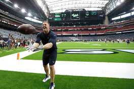 Houston Texans defensive end J.J. Watt tosses the ball to fans before the start of an NLF preseason game at NRG Stadium, Saturday, August 18, 2018, in Houston.