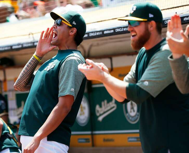 Oakland Athletics starting pitcher Sean Manaea (55) cheers as A's Khris Davis (2) doubles on a line drive to left field to score Marcus Semien and Jed Lowrie during the first inning of an MLB game between the Oakland Athletics and Houston Astros at the Oakland�Alameda County Coliseum on Saturday, Aug. 18, 2018, in Oakland, Calif.