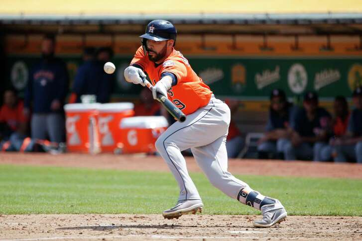 Houston Astros left fielder Marwin Gonzalez (9) bunts for an out during an MLB game between the Oakland Athletics and Houston Astros at the OaklandÐAlameda County Coliseum on Saturday, Aug. 18, 2018, in Oakland, Calif.