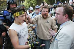"""Counter-protester Chase Cross, right, argues with members from right-wing groups Washington 3 Percenters and Patriot Prayer during a """"Liberty or Death"""" rally at Seattle City Hall, in part, to oppose Washington gun-control Initiative 1639, Saturday, Aug. 18, 2018. Counter-protesters lined the other side of the street, at least two men were arrested."""