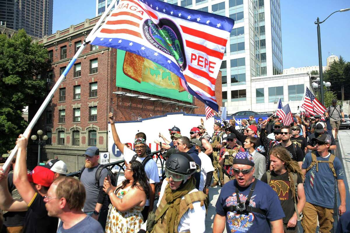 Protesters from right-wing groups Washington 3 Percenters and Patriot Prayer march down Yesler Way during a