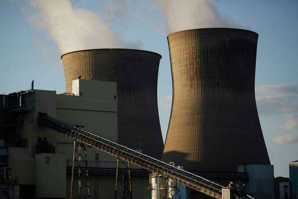 Steam rises from cooling towers at the American Electric Power Co. coal-fired power plant in Winfield, W.Va., on July 18.