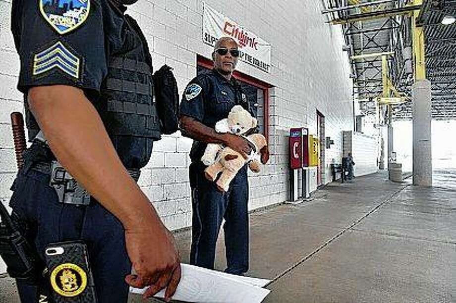 Peoria police officer Curtis Lindsay talks with another officer as he waits for buses to arrive at the CityLink Mass Transit Center to hand out stuffed animals to children. Lindsay has been passing to stuffed animals to children he encounters for the past year while on his rounds. Photo:       David Zalaznik | Journal Star (AP)
