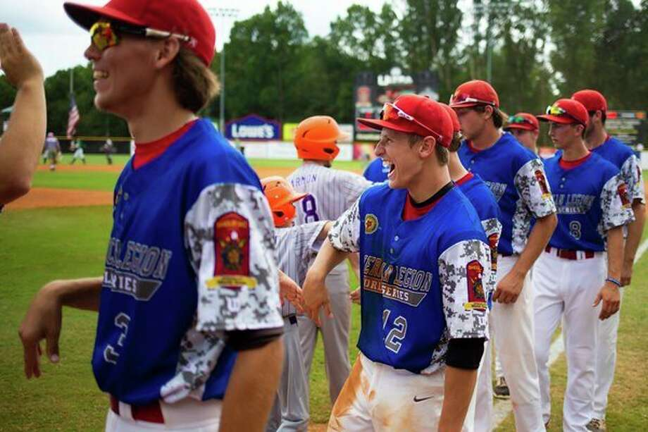 Berryhill's Logan LaCourse laughs while high-fiving a Post 165 bat boy following a 3-2 win over Las Vegas, Nev., Saturday at the American Legion Baseball World Series in Shelby, N.C. (Chet Strange/The American Legion) / Copyright 2018 Chet Strange / The American Legion