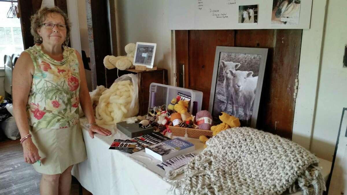 Riverton Grange Fair secretary Raine Pedersen, 63, at the educational sheep table display she had created with Jason and Teresa Fuller of Riverton?'s Grassy Knoll Farm Saturday afternoon.