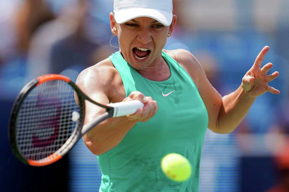 Simona Halep, of Romania, returns to Kiki Bertens, of the Netherlands, during the finals at the Western & Southern Open tennis tournament, Sunday, Aug. 19, 2018, in Mason, Ohio.